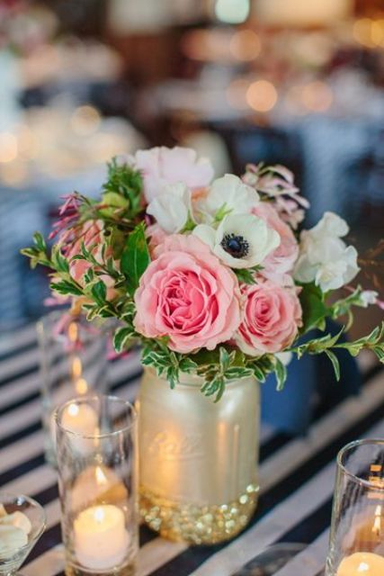 a gold and glittered mason jar with pink and white flowers