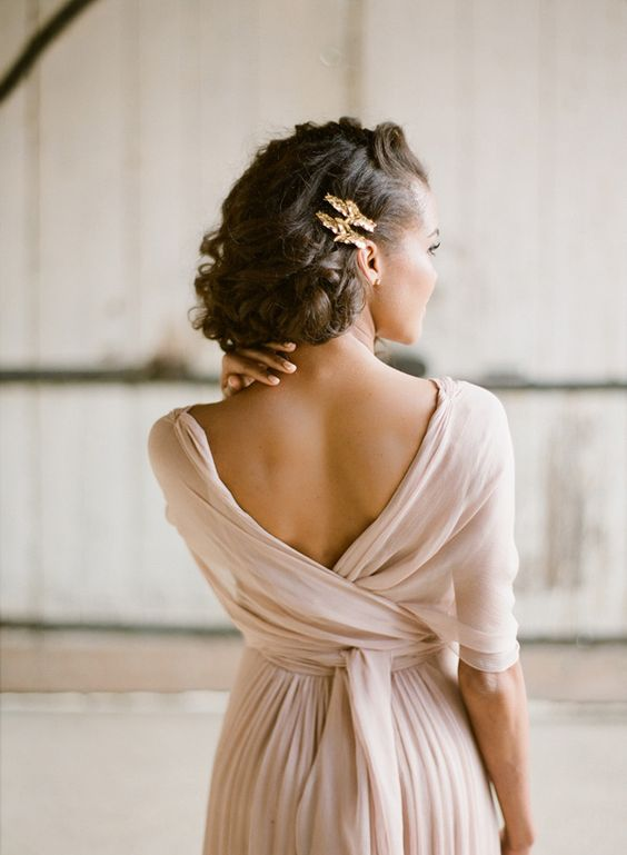 elegant soft rolled bridal updo with a couple of copper hairpins