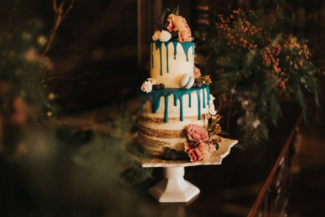 The semi naked wedding cake with emerald dripping, macarons and large blooms