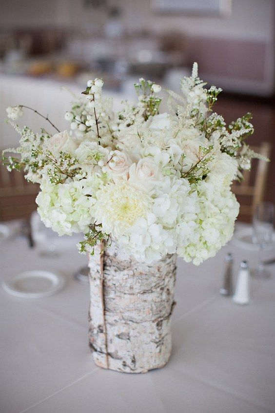 a birch covered vase with blush and white flowers