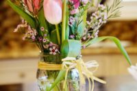 10 a mason jar with pink tulips, herbs and various small flowers