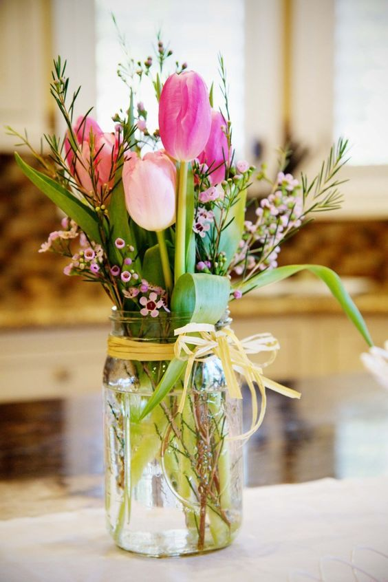 a mason jar with pink tulips, herbs and various small flowers