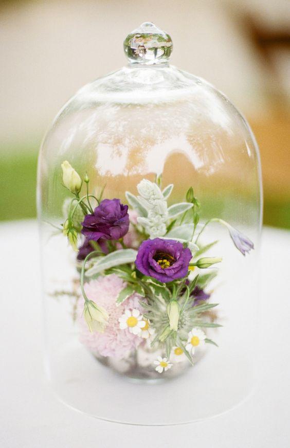 a floral arrangement displayed under a cloche