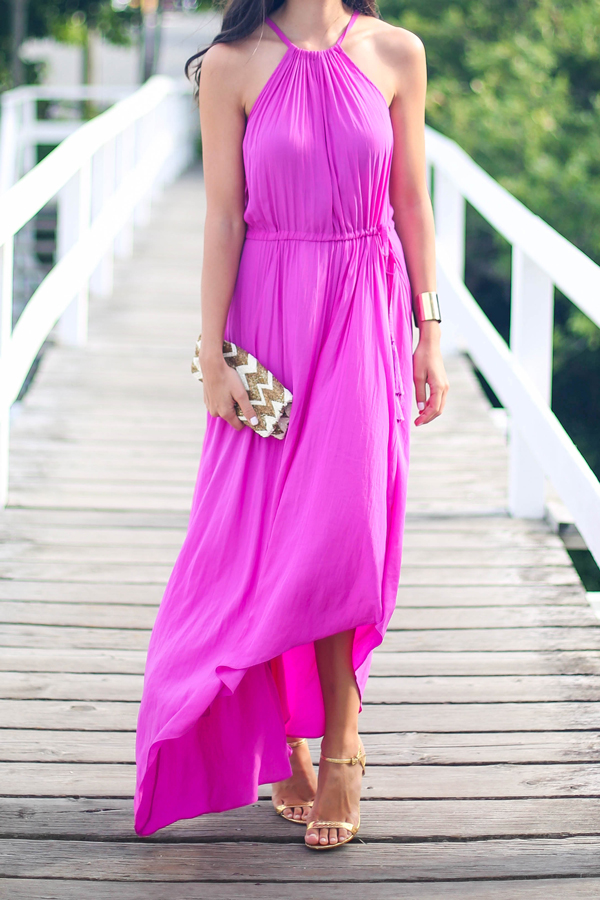 a halter neckline fuchsia dress with nude heels and a cute clutch