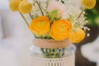 11 a mason jar wrapped with a doily with a bold yellow and white floral arrangement