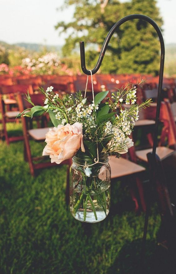 a rustic floral arrangement in a mason jar for fresh aisle decor