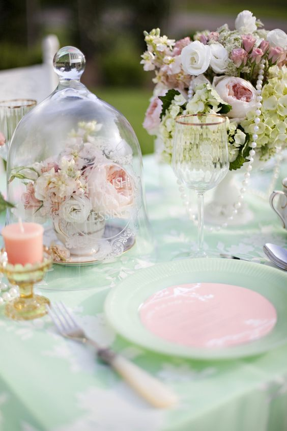 a cloche with pastel flowers in a vintage tea cup