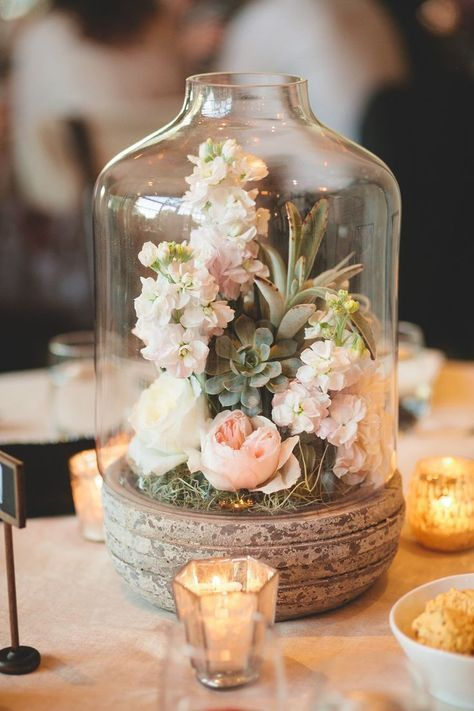 a jar on a wooden stand and moss, succulents and fresh blooms inside