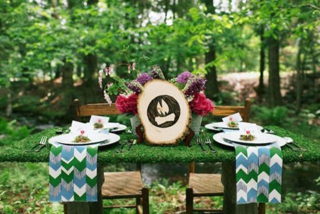 a small moss covered table with bold flowers and a wood slice sign