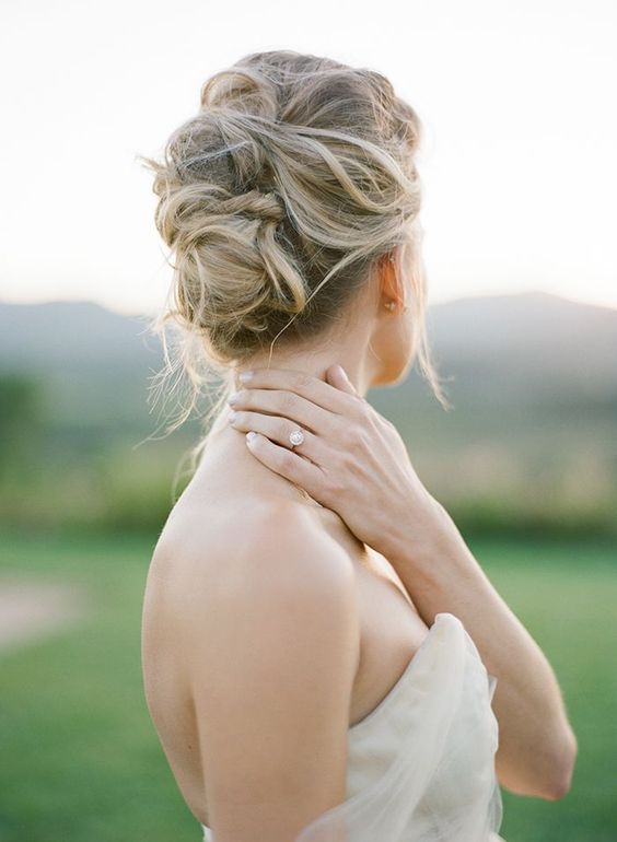 a soft and messy bridal updo looks chic and doesn't require much effort to make