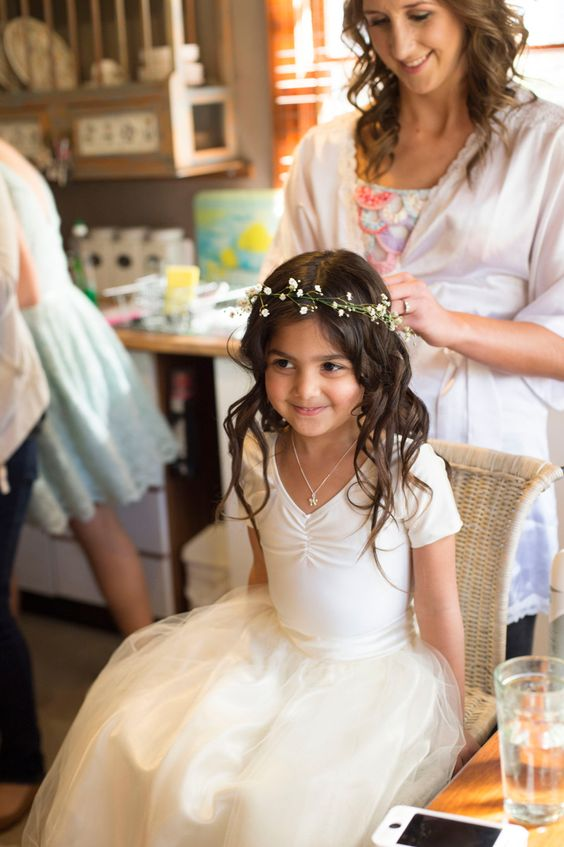 an ivory dress with short sleeves and a tulle skirt, a baby's breath crown