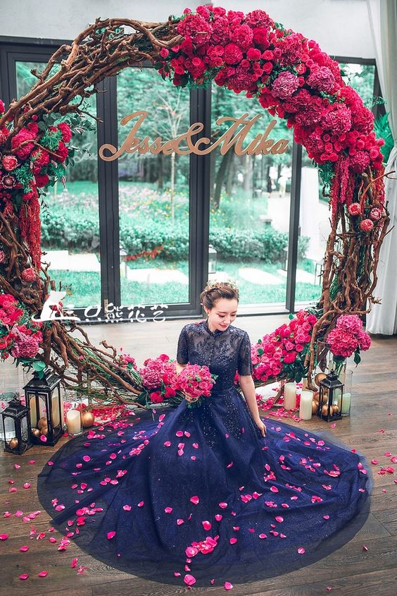 gorgeous bold red and fuchsia wreath as a wedding backdrop, lanterns and candles all around