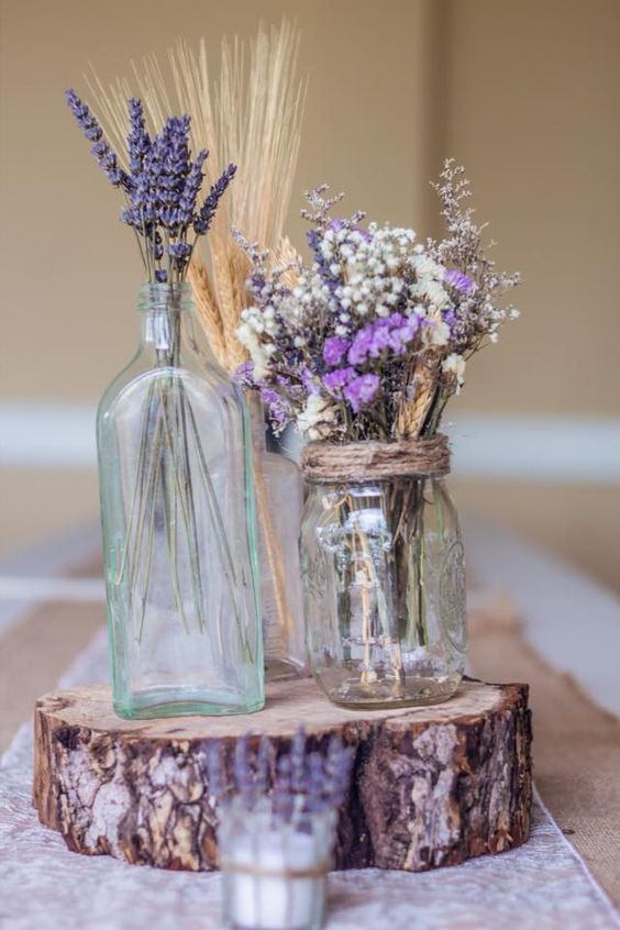 mason jars with lavender and wheat on a wood slice