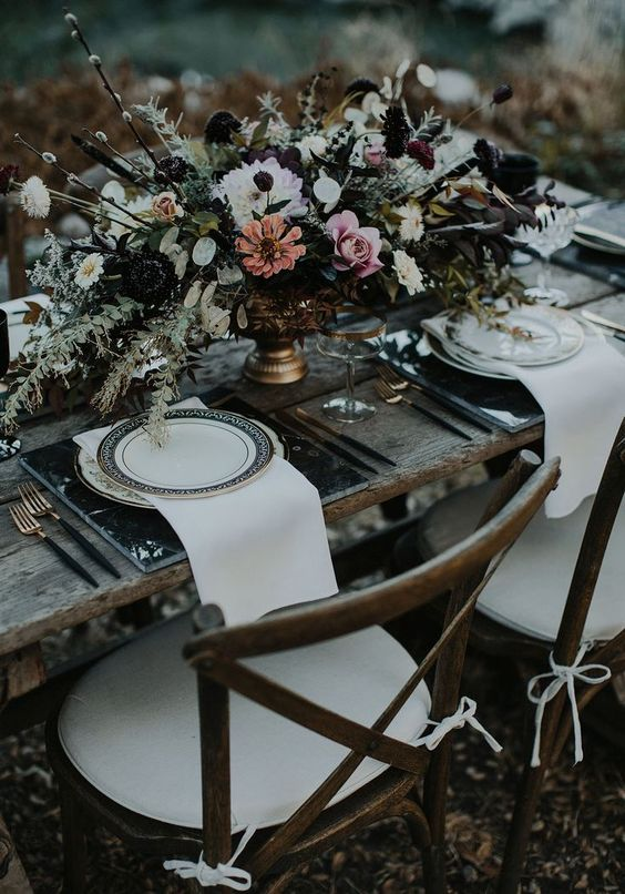 a dark floral arrangement with willow and black blooms