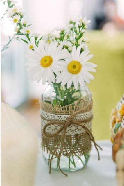 a mason jar with burlap and lace and camellias