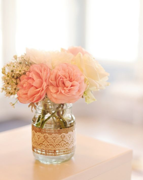 a mason jar wrapped with burlap and lace with blush and neutral flowers