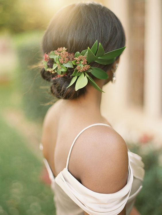 a rolled updo with fresh green leaves
