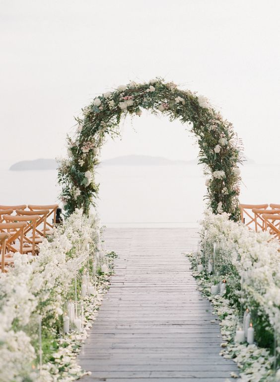 messy wedding arch covered with greenery, white and pink blooms and the aisle lined with white flowers