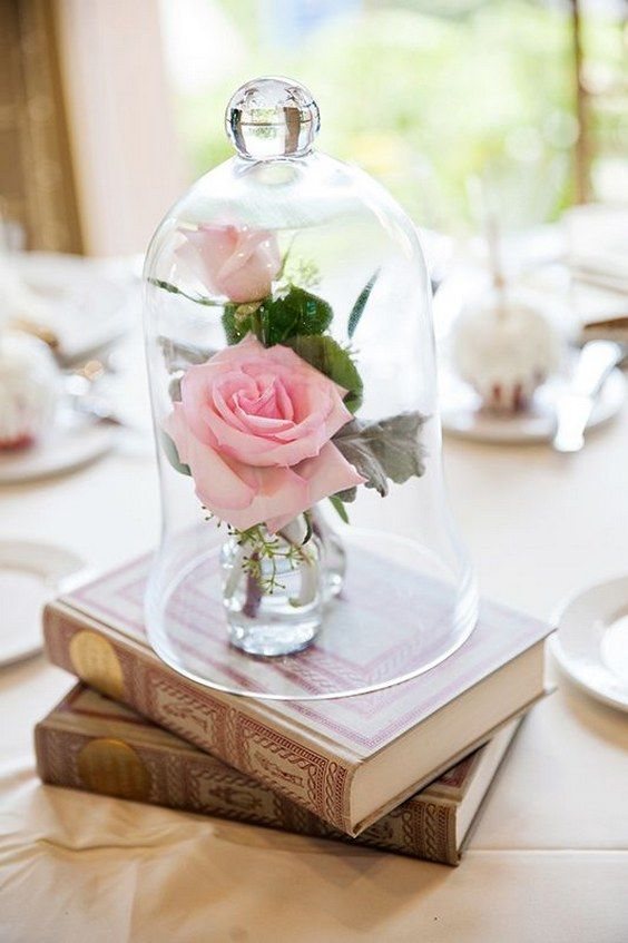 vintage books and pink roses in a cloche is a refined idea