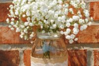 14 a mason jar wrapped with burlap and some lace and baby's breath