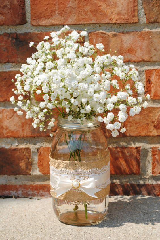 a mason jar wrapped with burlap and some lace and baby's breath