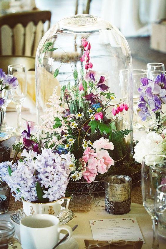 a wildflower arrangement in a cloche for a garden or woodland wedding