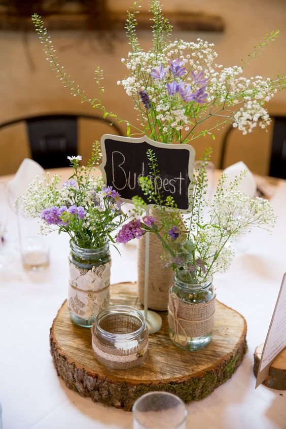 a wood slice with mason jars covered with burlap and with fresh flowers inside