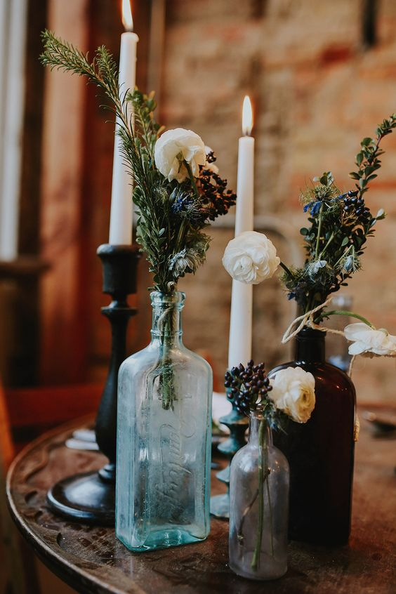simple bottles with evergreens and wildflowers and candles