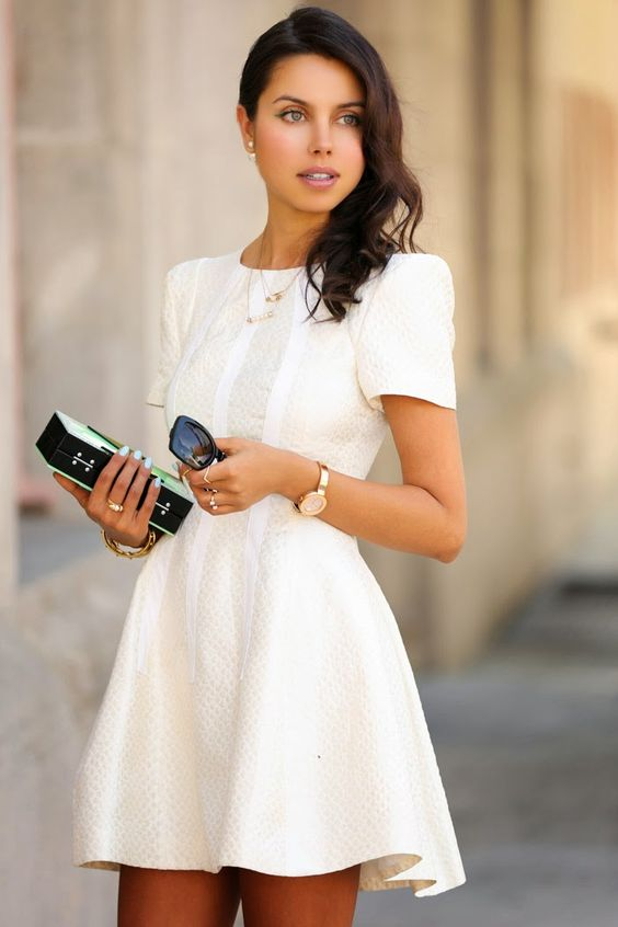 a textured ivory skater dress with short sleeves and layered necklaces