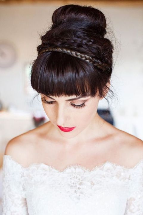 a top knot with several thin braids and a fringe