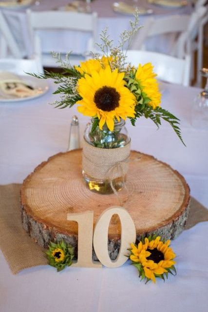 a wood slice with a mason jar, burlap and sunflowers