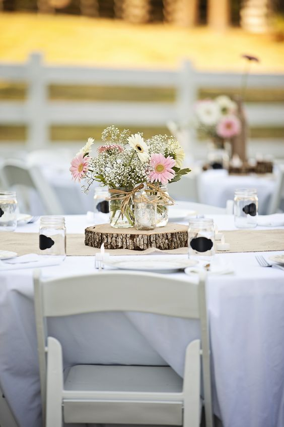 a wood slice with mason jars and simple florals