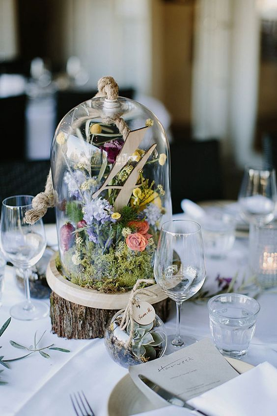 a woodland centerpiece with moss, wildflowers and billy balls plus a wooden table number