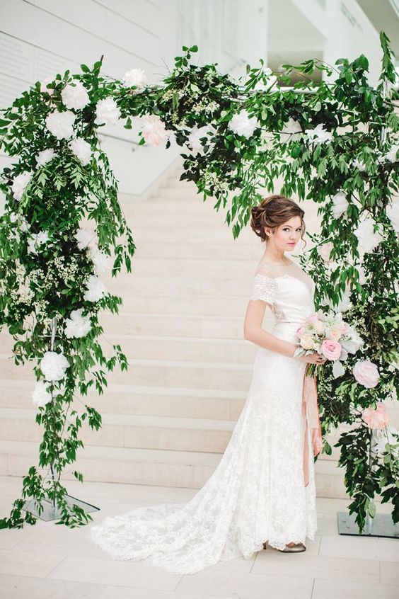 lush greenery and white flower wedding arch looks very chic and fresh