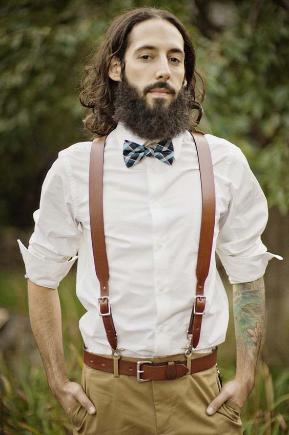 ocher pants, a white shirt, brown leather suspenders and a matching belt, a colorful bow tie