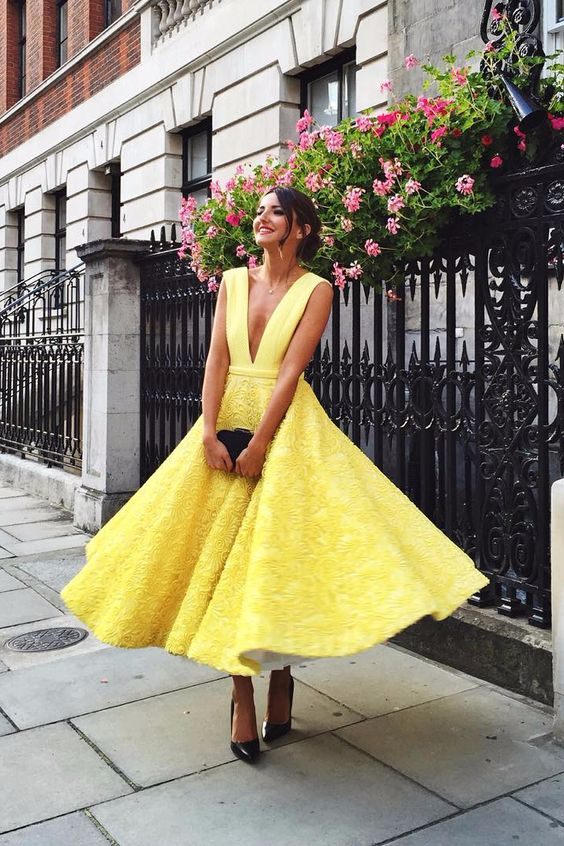 sunny yellow midi dress with a plunging neckline and a textural skirt, black shoes and a clutch