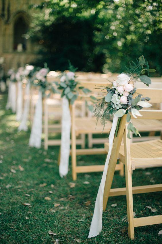 white flowers, leaves and white ribbon for an elegant summer aisle