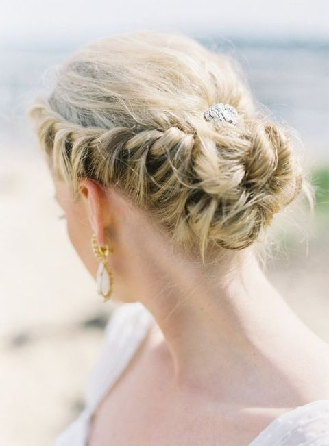 a braided updo with a hairpiece in the center looks chic