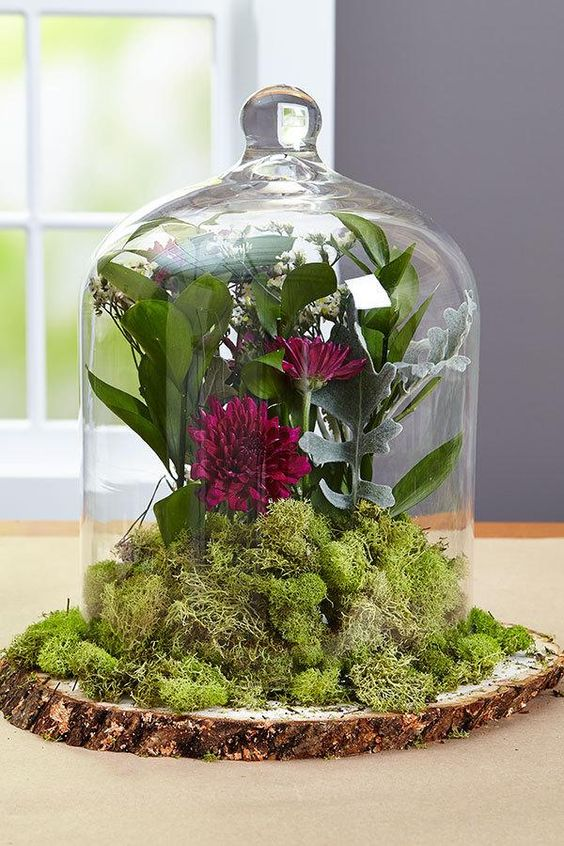a rustic centerpiece with a wood slice, moss and dark flowers