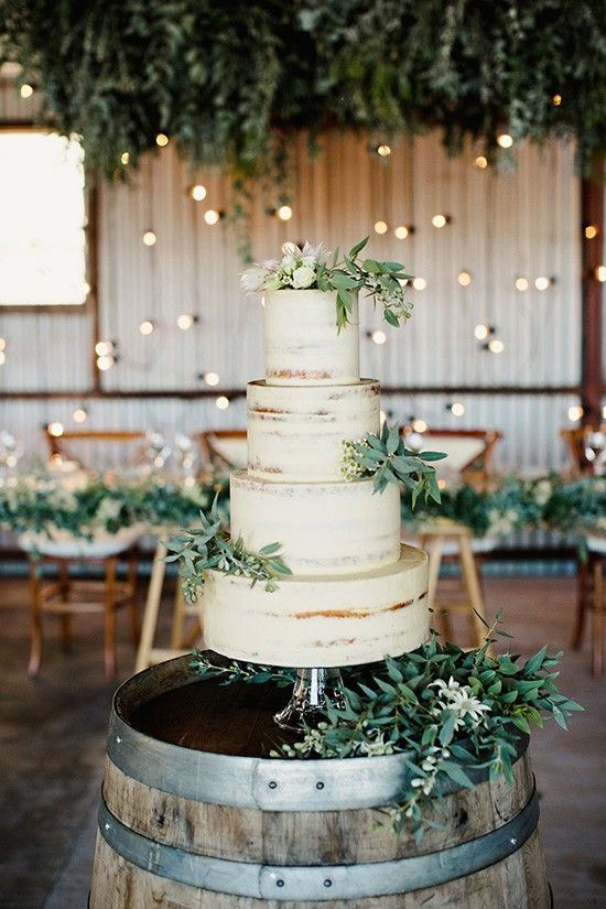 a semi naked wedding cake with greenery