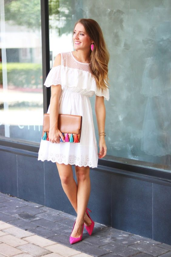 a white cold-shoulder dress with crochet lace, hot pink shoes and a clutch with tassels