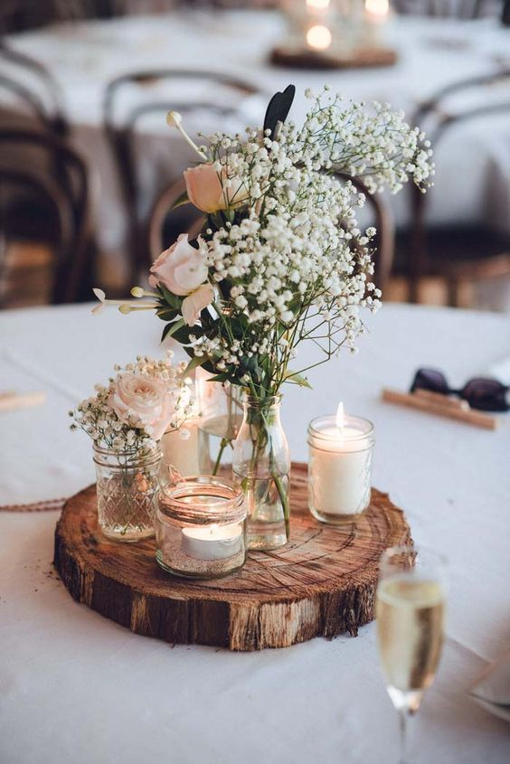 a wooden slice with candles and a floral centerpiece of roses and baby's breath