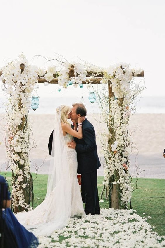 lush white floral wedding arch and flower petals on the aisle