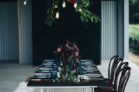 16 moody table setting with greenery, burgundy flowers and industrial bulbs over it