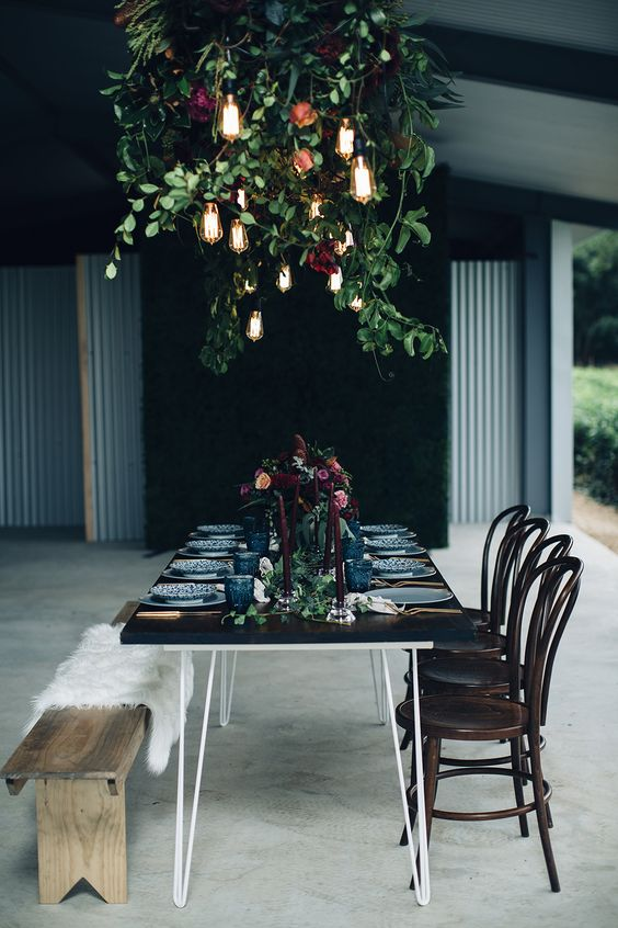 moody table setting with greenery, burgundy flowers and industrial bulbs over it