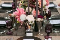 17 a dark tablescape with chocolate-colored plates, candles and silver glasses
