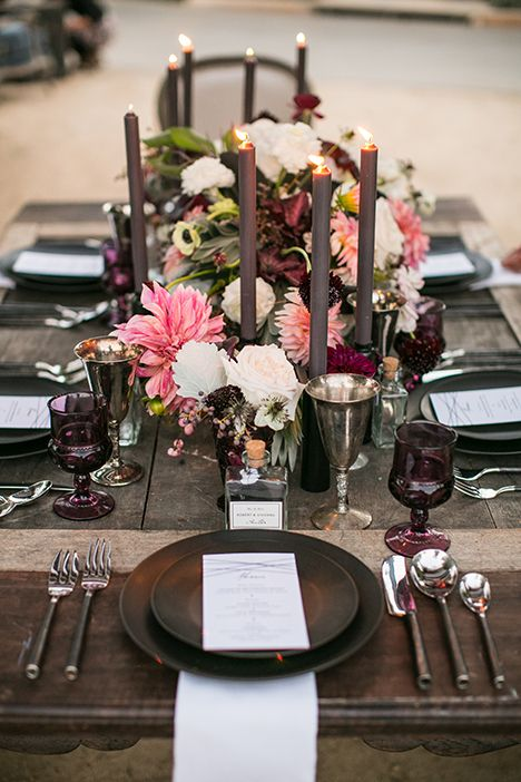 a dark tablescape with chocolate-colored plates, candles and silver glasses