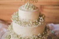 17 a white cake decorated with baby's breath and a wooden topper