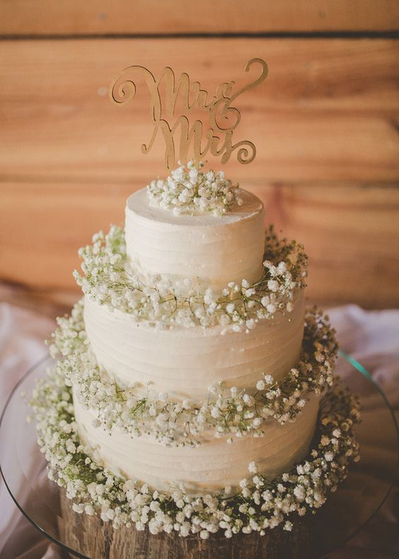 a white cake decorated with baby's breath and a wooden topper