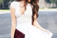 17 a white dress with a lace bodice and cap sleeves, a deep V cut, a burgundy clutch